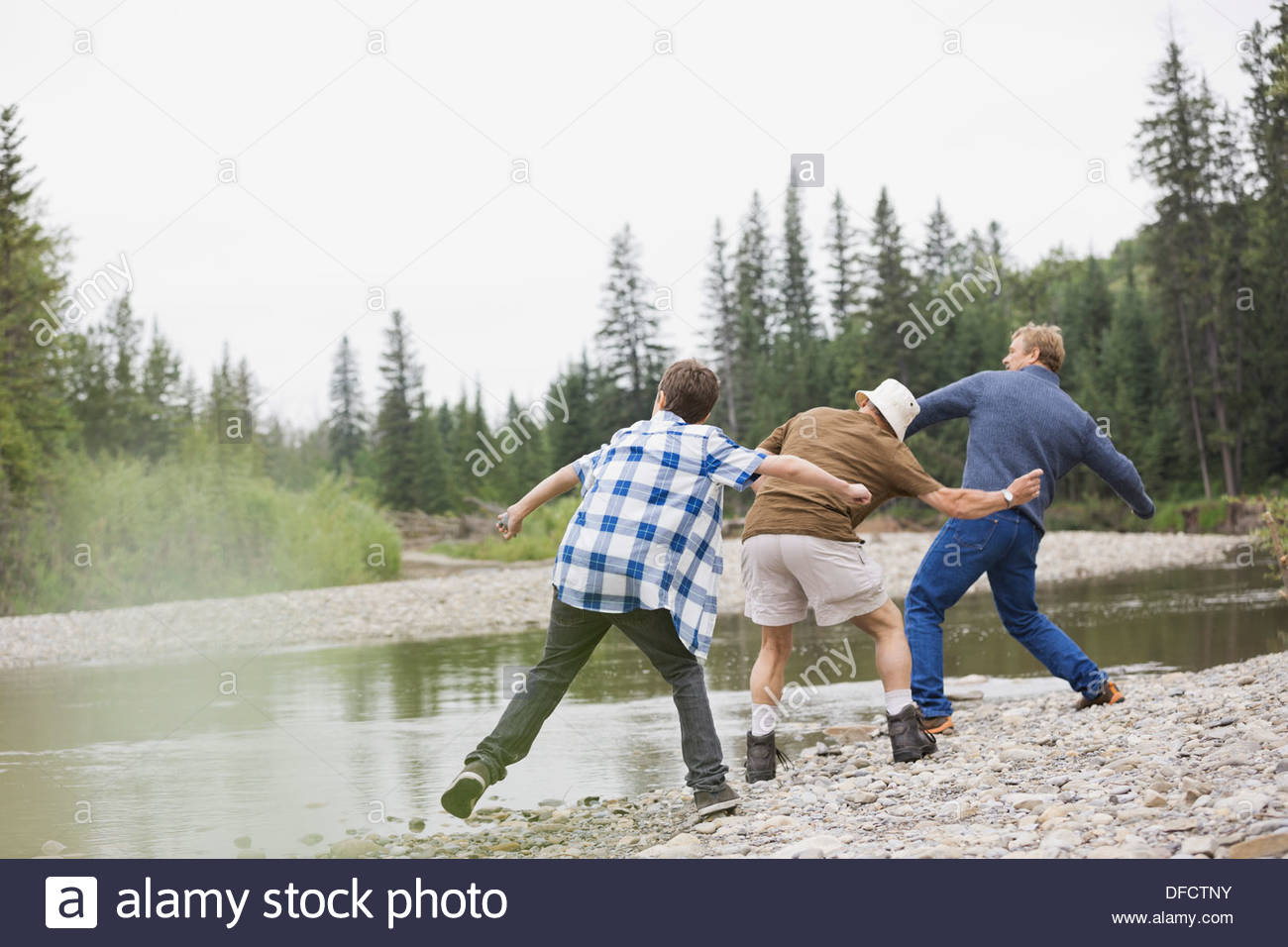 Male family members skipping rocks on a river - Stock Image
