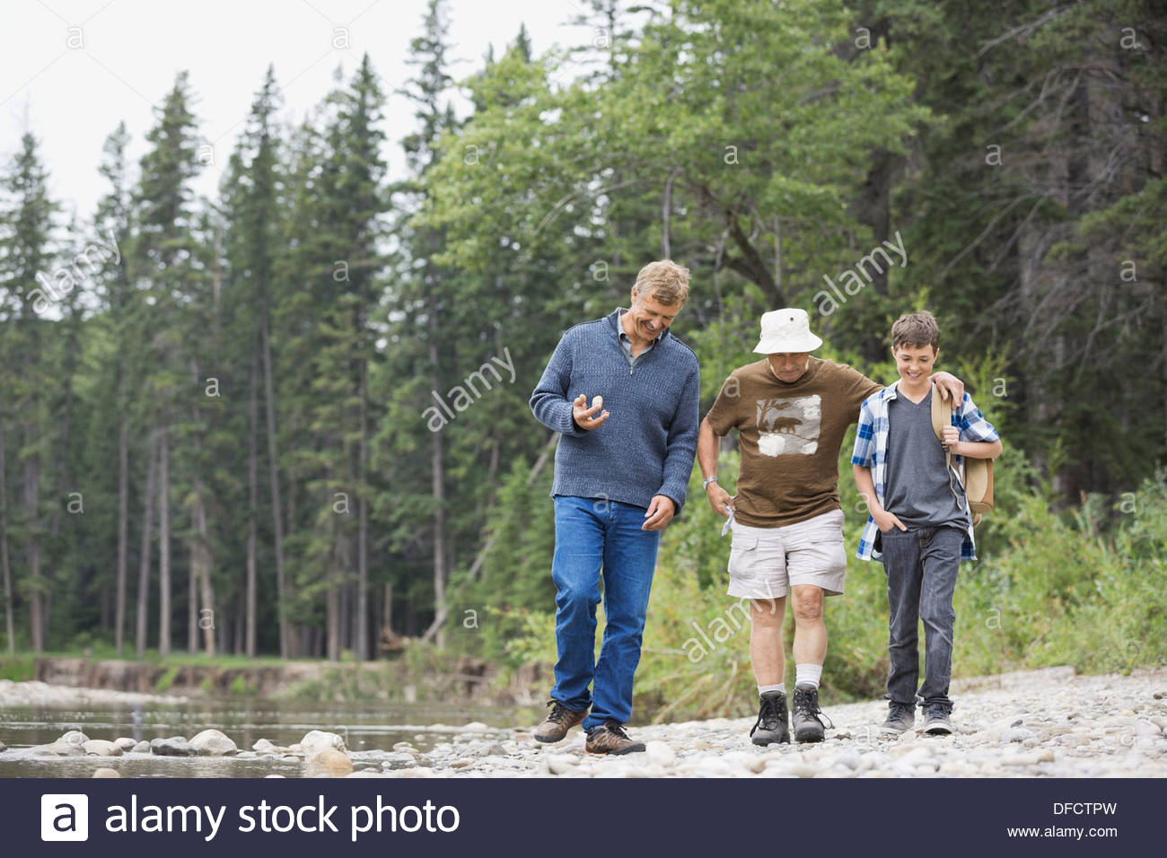 Three generation males walking on river bank - Stock Image