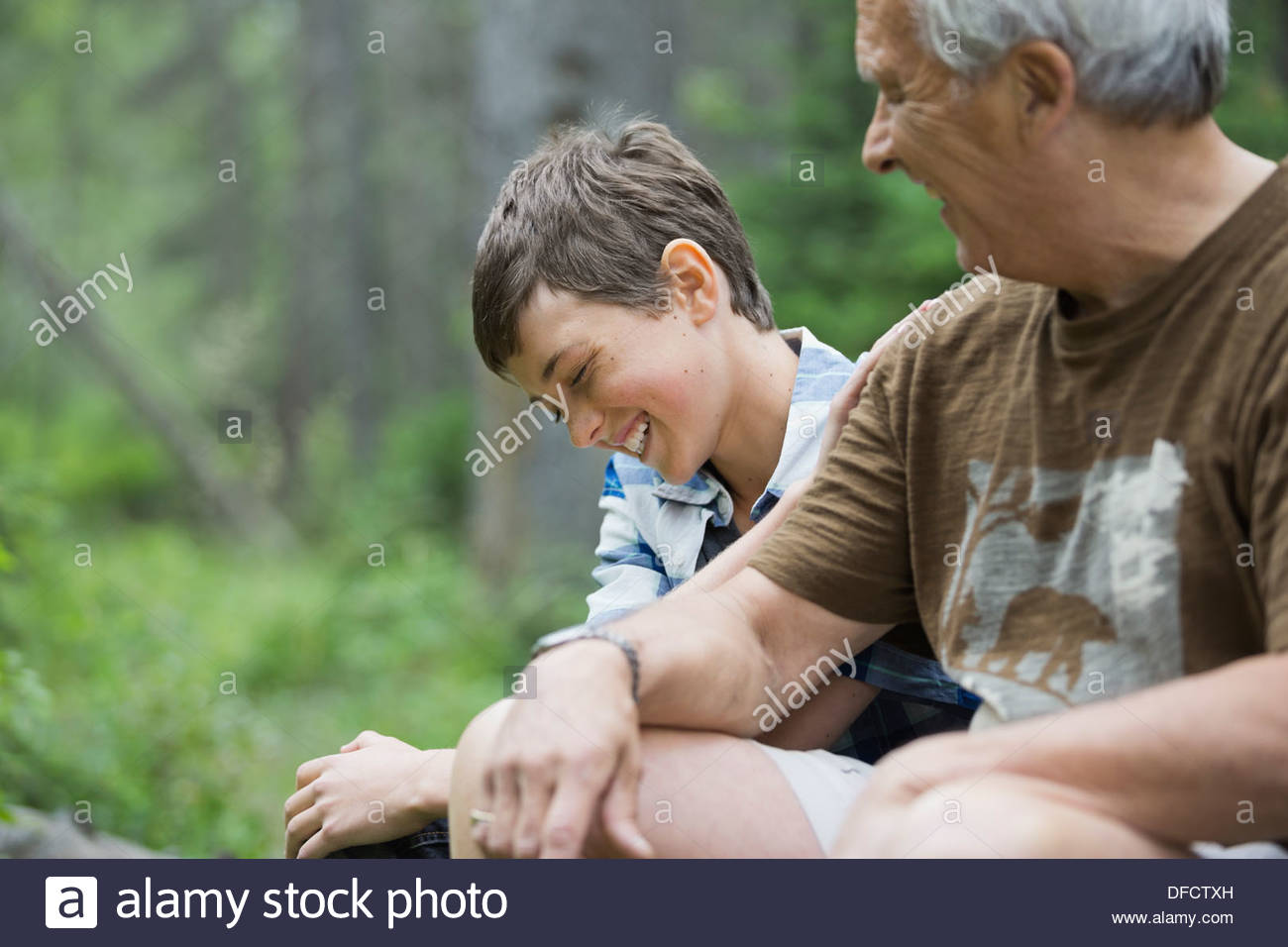 Happy boy sitting with grandfather in forest - Stock Image