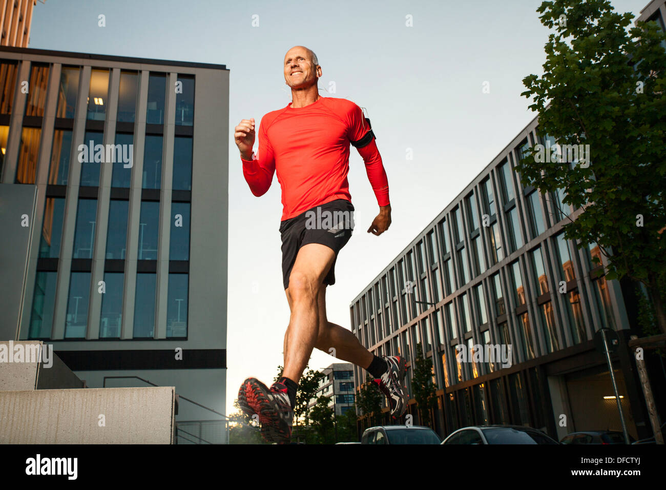 Mature athletic man running on stairs - Stock Image