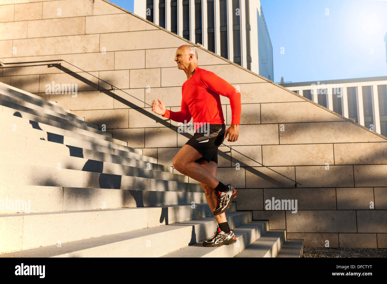 Mature athletic man running upstairs - Stock Image