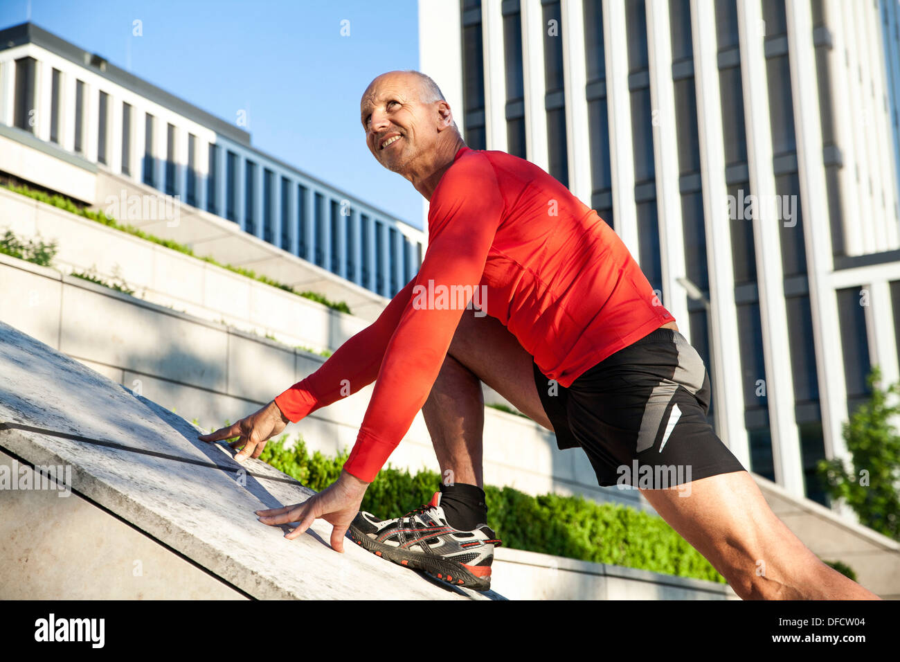 Mature athletic man stretching outdoors - Stock Image