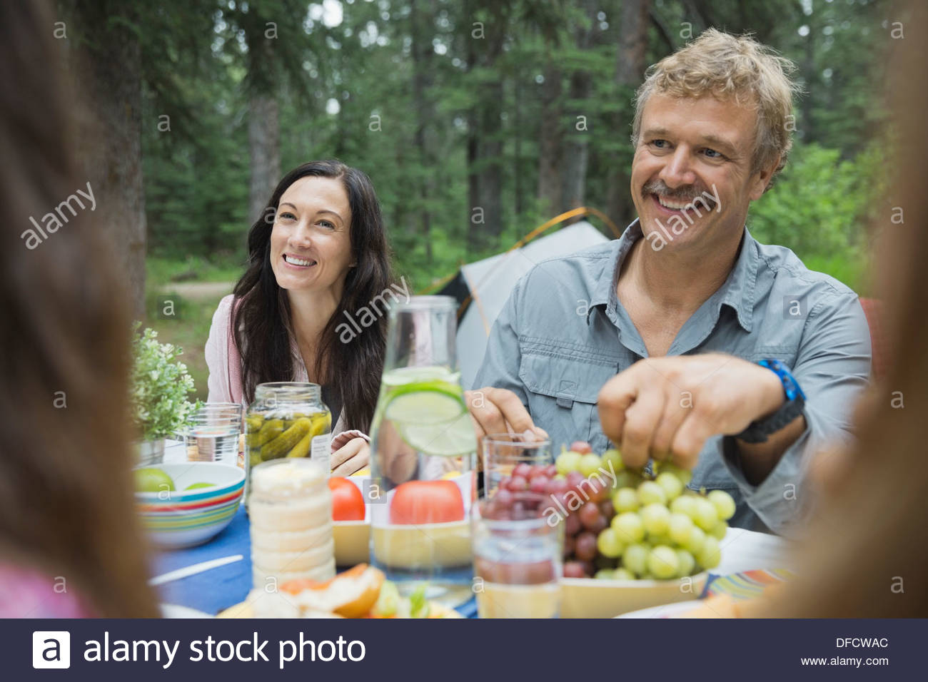 Couple having meal with family at campsite - Stock Image