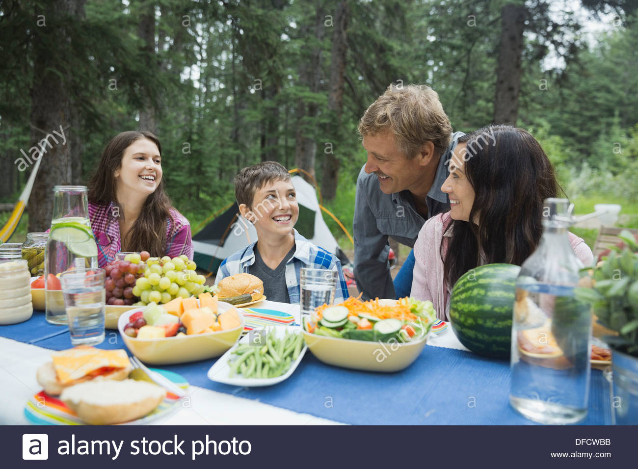 Happy family of four having meal at campsite - Stock Image