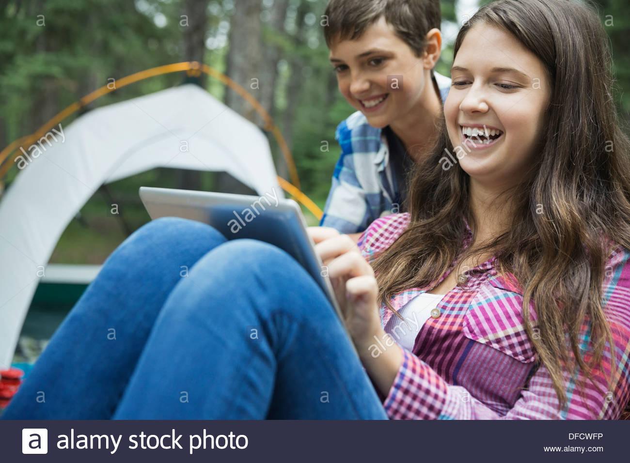 Siblings watching digital tablet at campsite Stock Photo