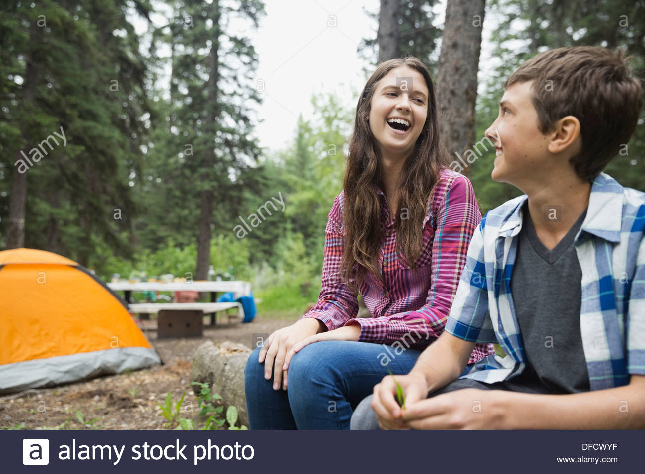 Cheerful siblings sitting at campsite - Stock Image