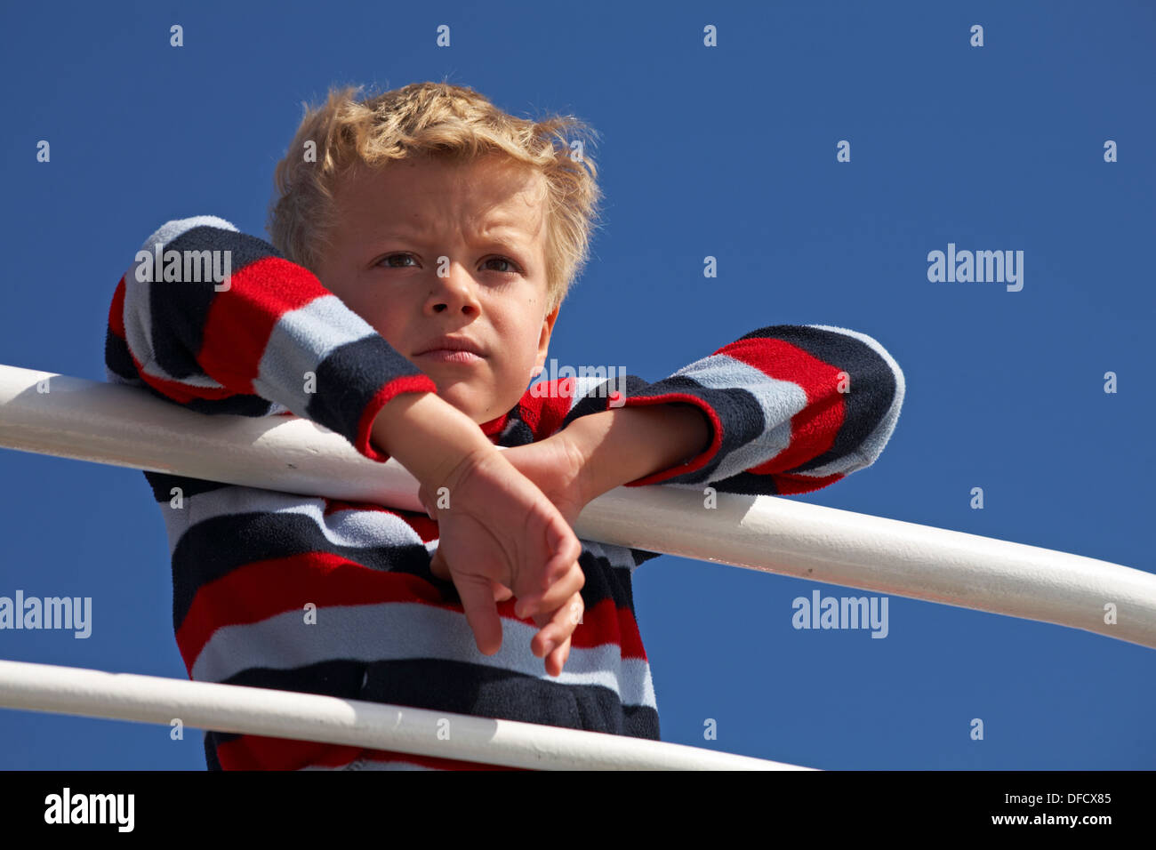Looking up at young lad leaning over railings to admire the view - Stock Image