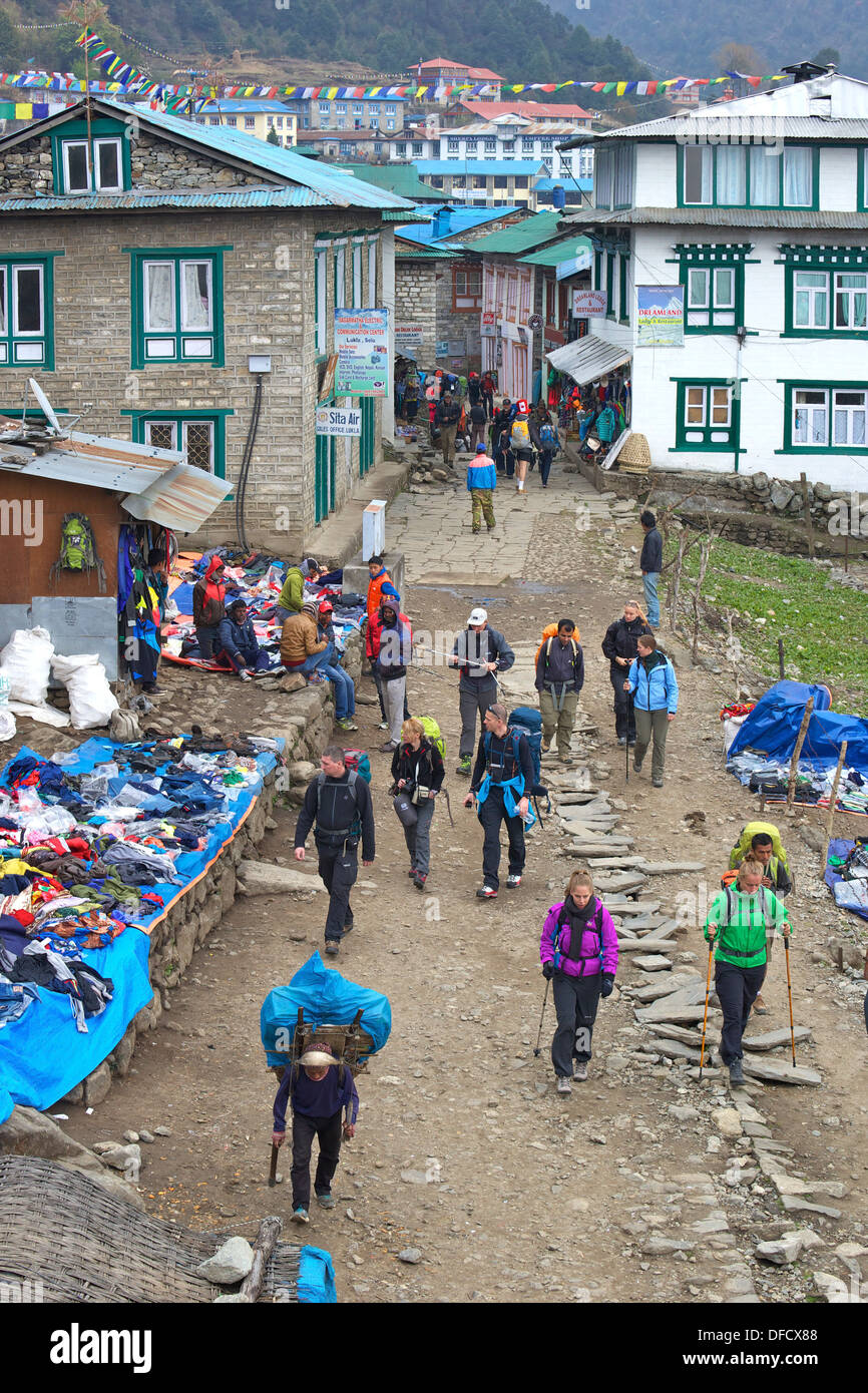 Trekkers and porters walking through town of Lukla, en route to Everest Base Camp trek, Nepal, Asia - Stock Image