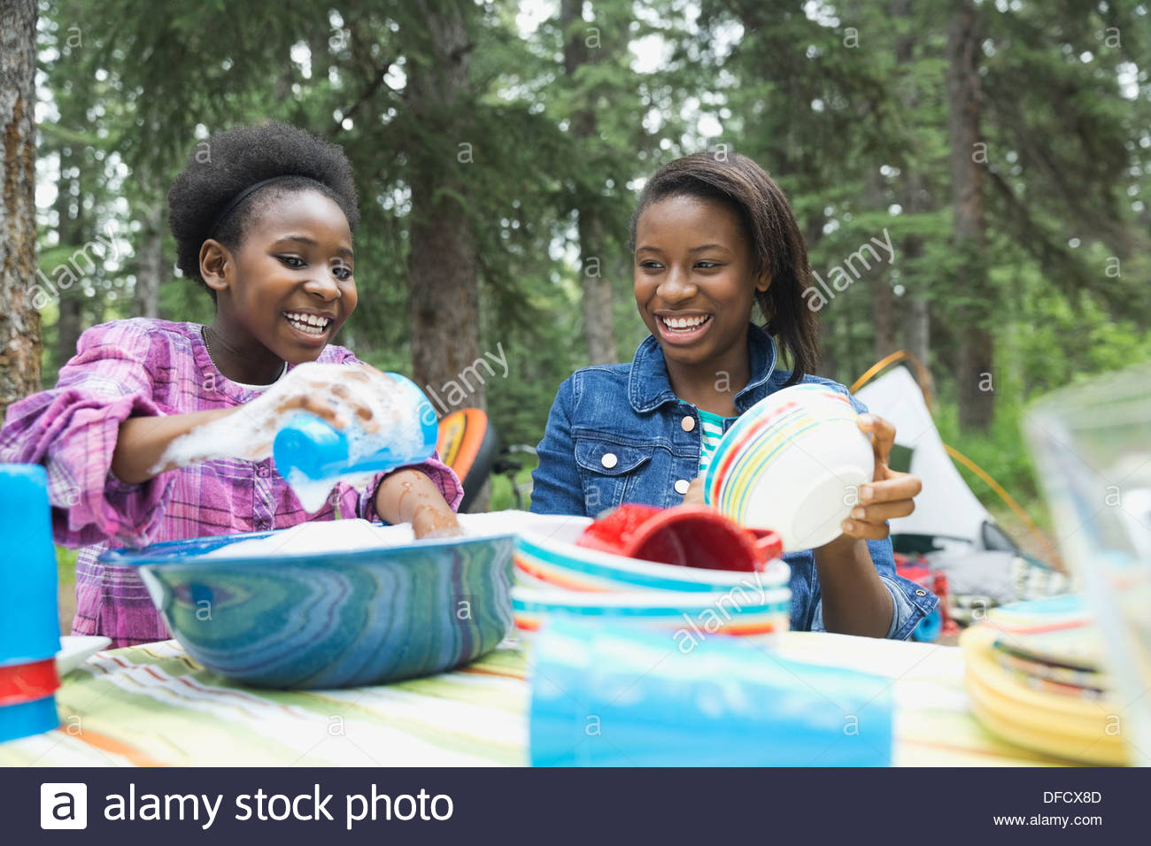 Happy sisters washing dishes at campsite - Stock Image
