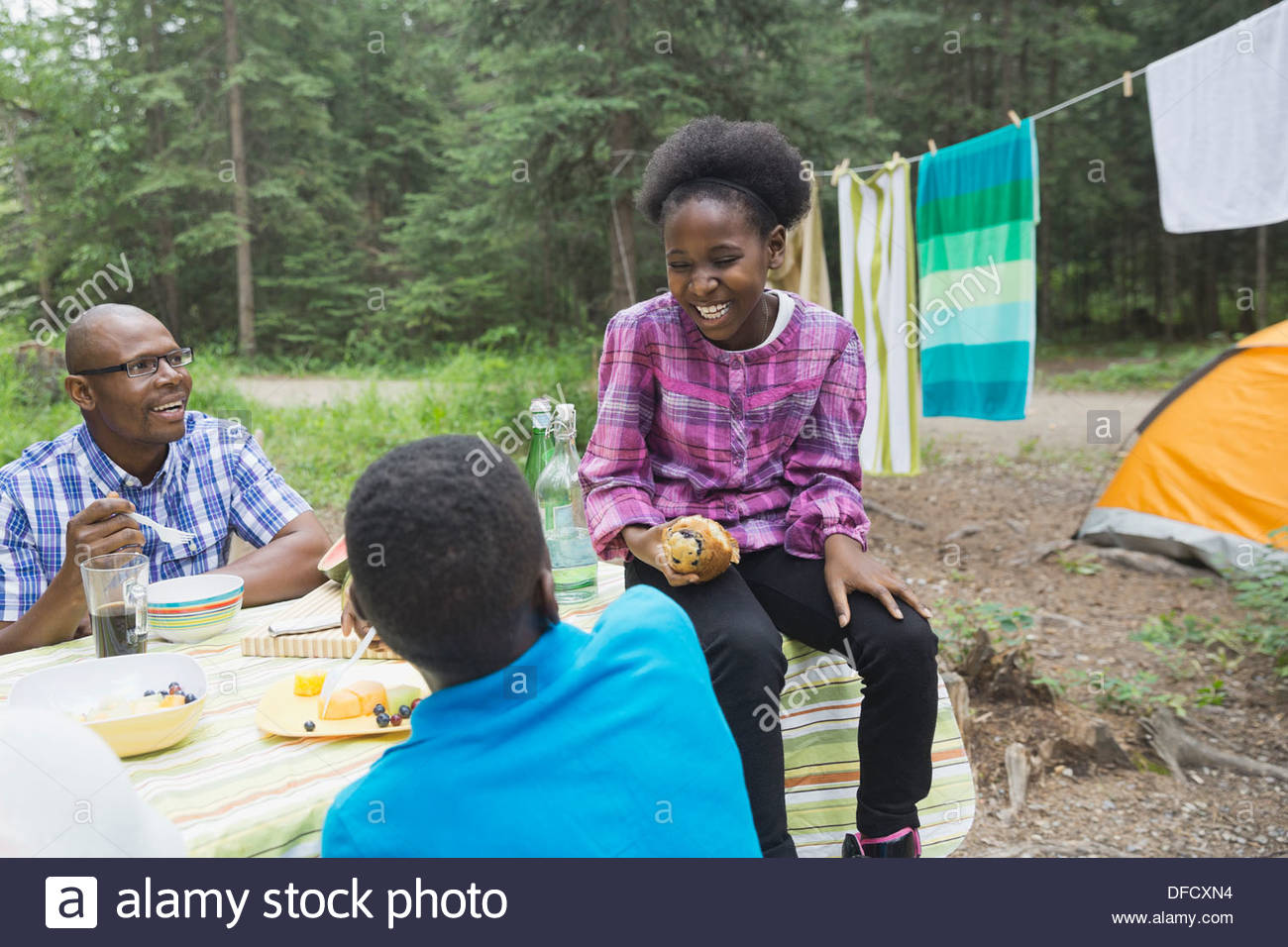 Happy children and father enjoying meal at campsite - Stock Image