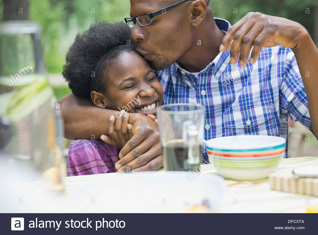 Father kissing daughters forehead - Stock Image