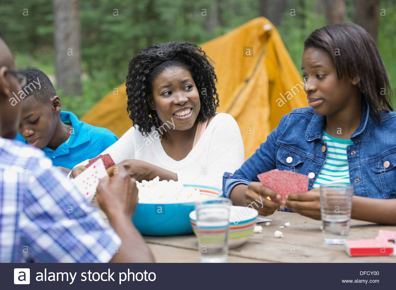 Family of four playing cards while camping - Stock Image