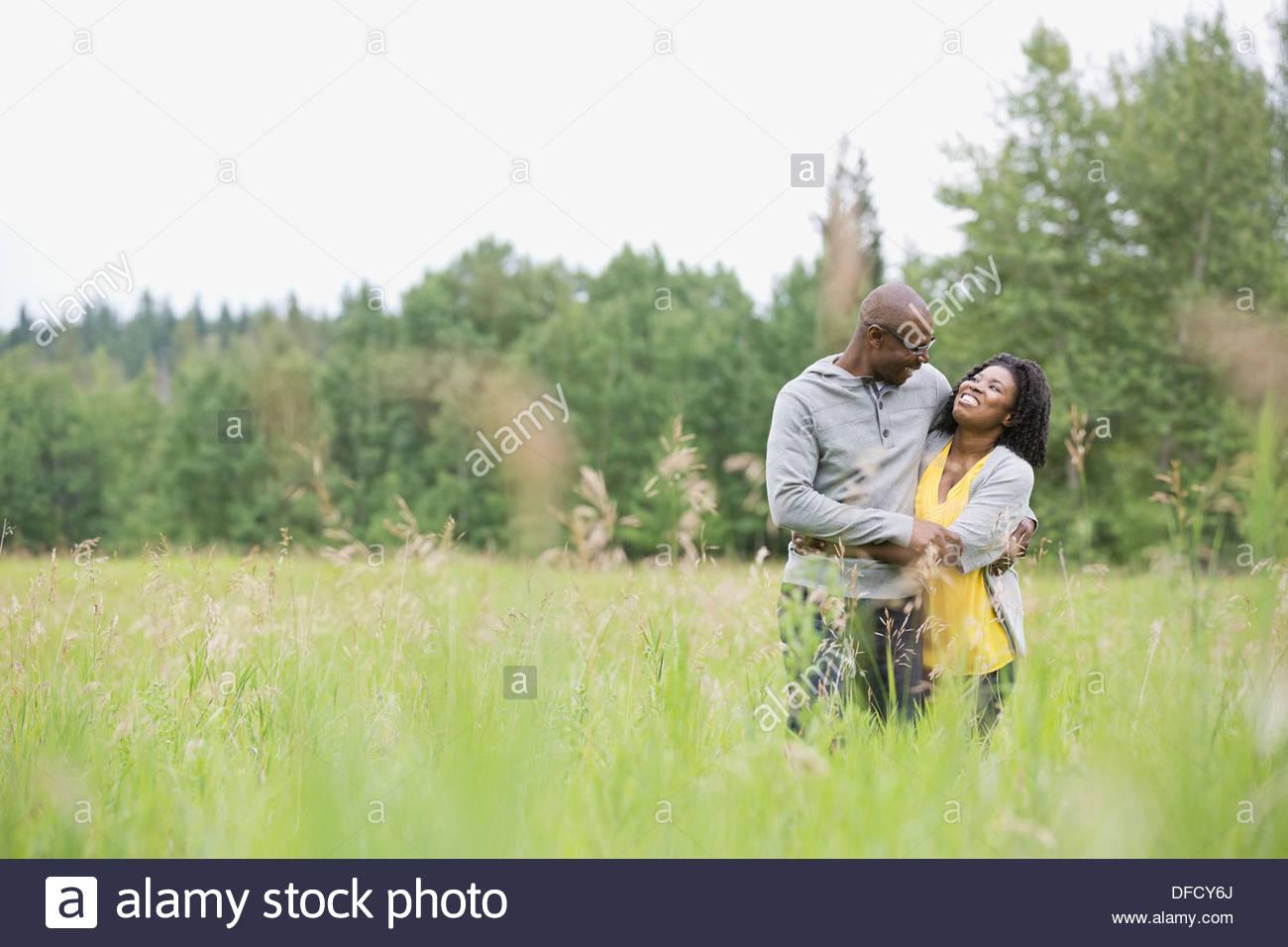 Woman embracing husband outdoors - Stock Image