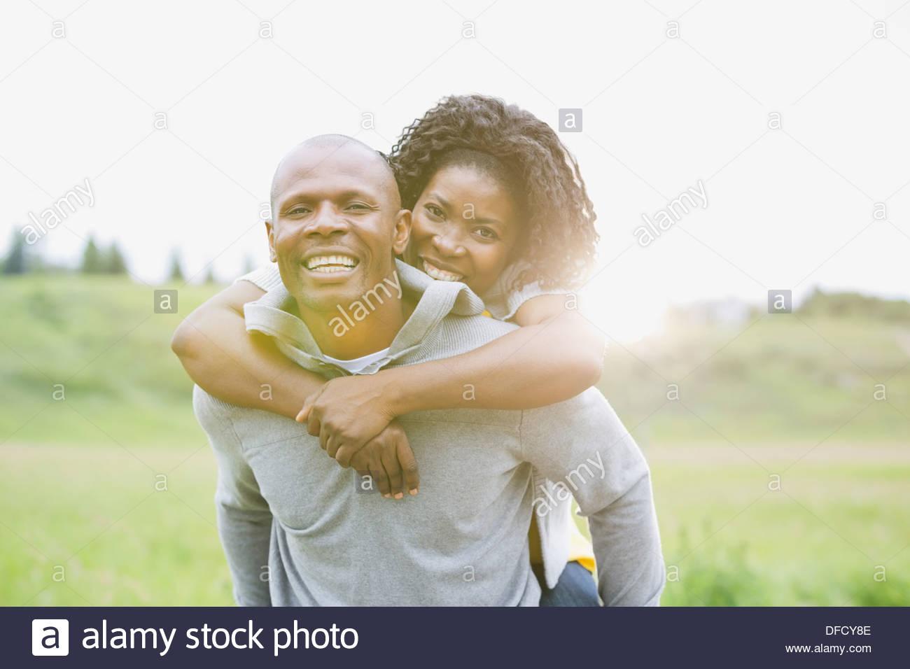 Husband piggybacking wife outdoors - Stock Image