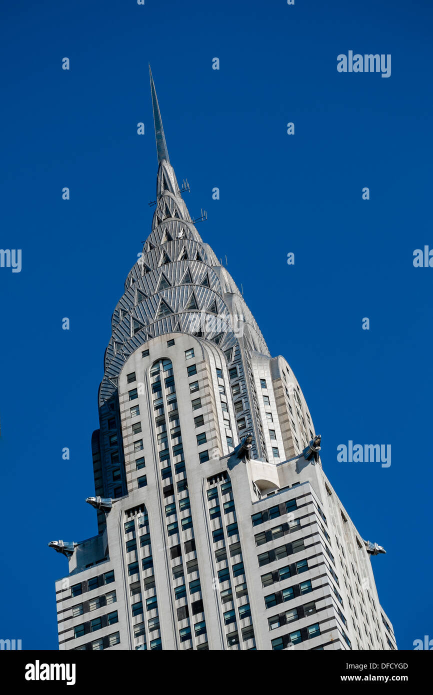 A close view of the Art Deco style architecture of the Chrysler Building in New York City against a blue sky. - Stock Image