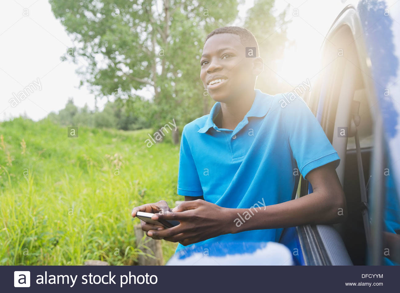 Boy leaning against car holding smart phone - Stock Image