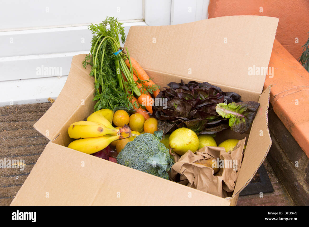 26 July 2013, Brighton, UK: An organic fruit and vegetable box delivered by Abel and Cole sits on a doorstep - Stock Image