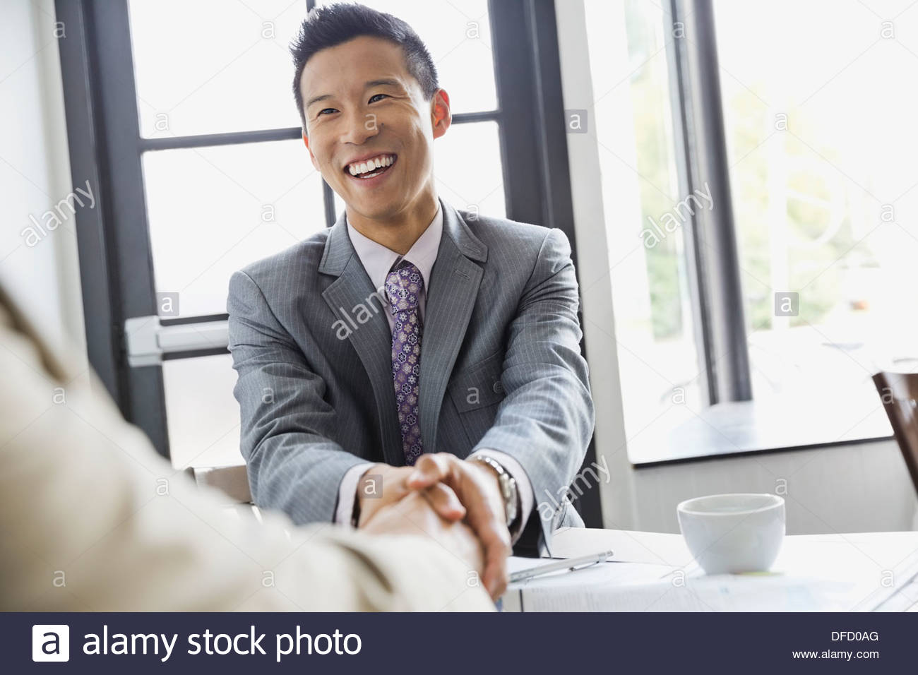 Businessman shaking hands with partner in restaurant - Stock Image