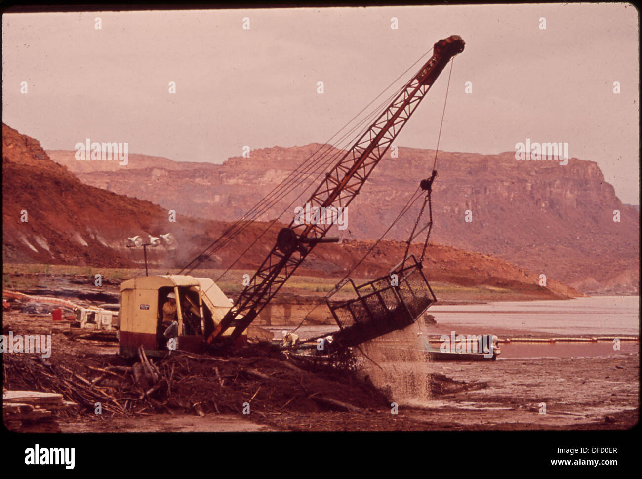 DRAGLINE SHOVEL SCOOPS UP OIL-LADEN DEBRIS FROM LOG BOOM ON SAN JUAN RIVER NEAR LAKE POWELL. OIL FLOWED FROM BURST... Stock Photo