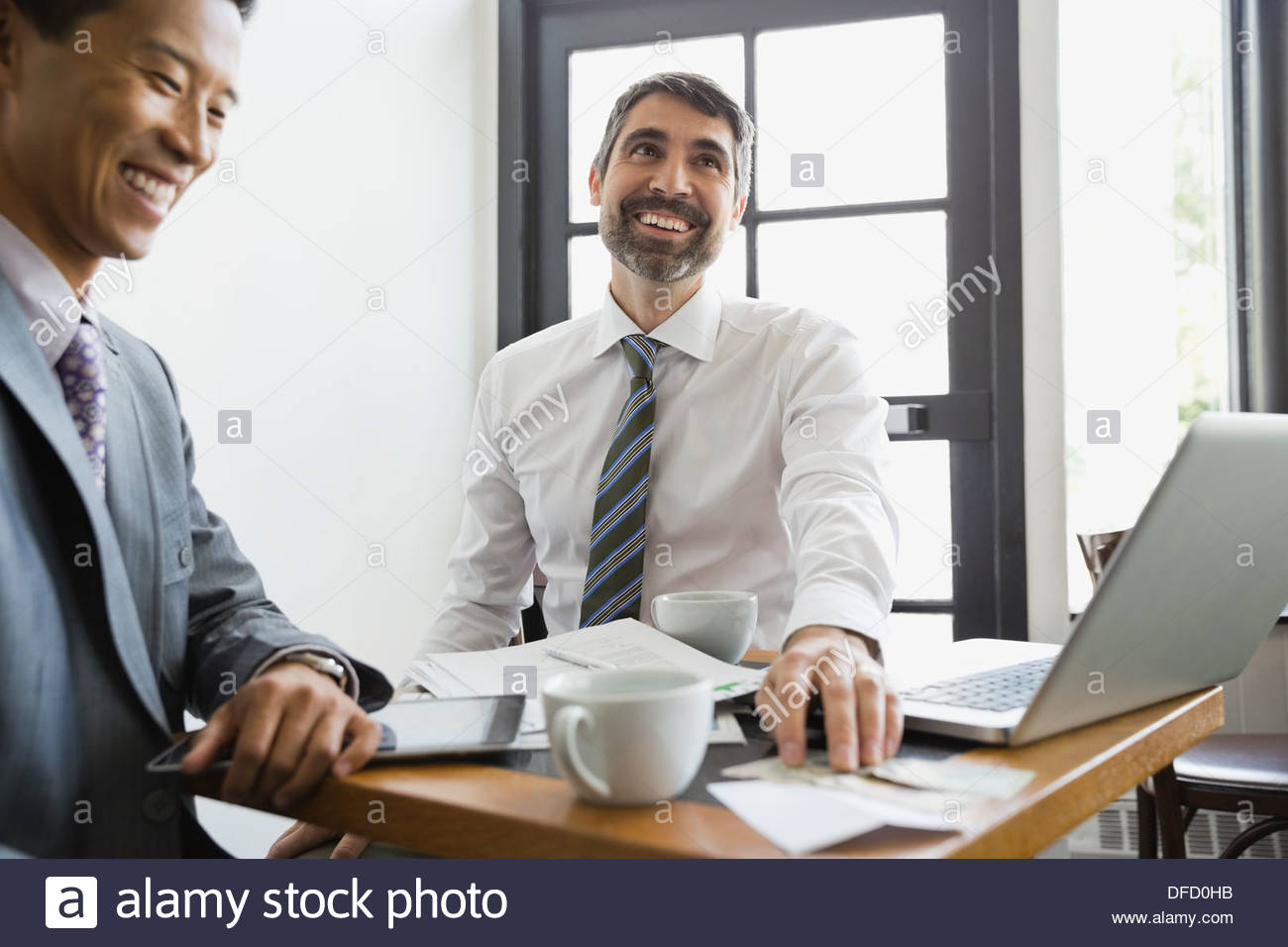 Businessmen paying restaurant bill with cash - Stock Image
