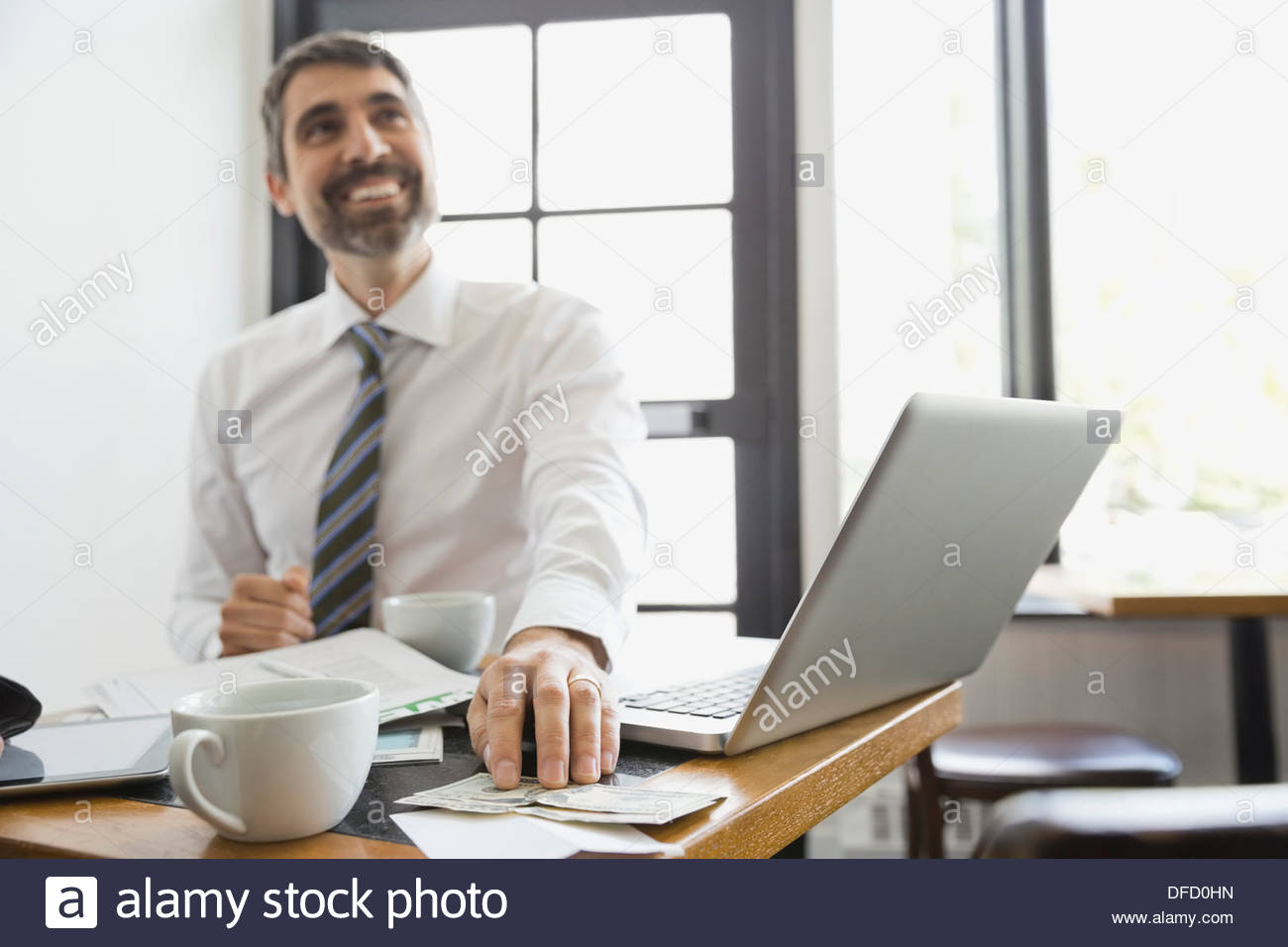 Businessman paying restaurant bill with cash - Stock Image