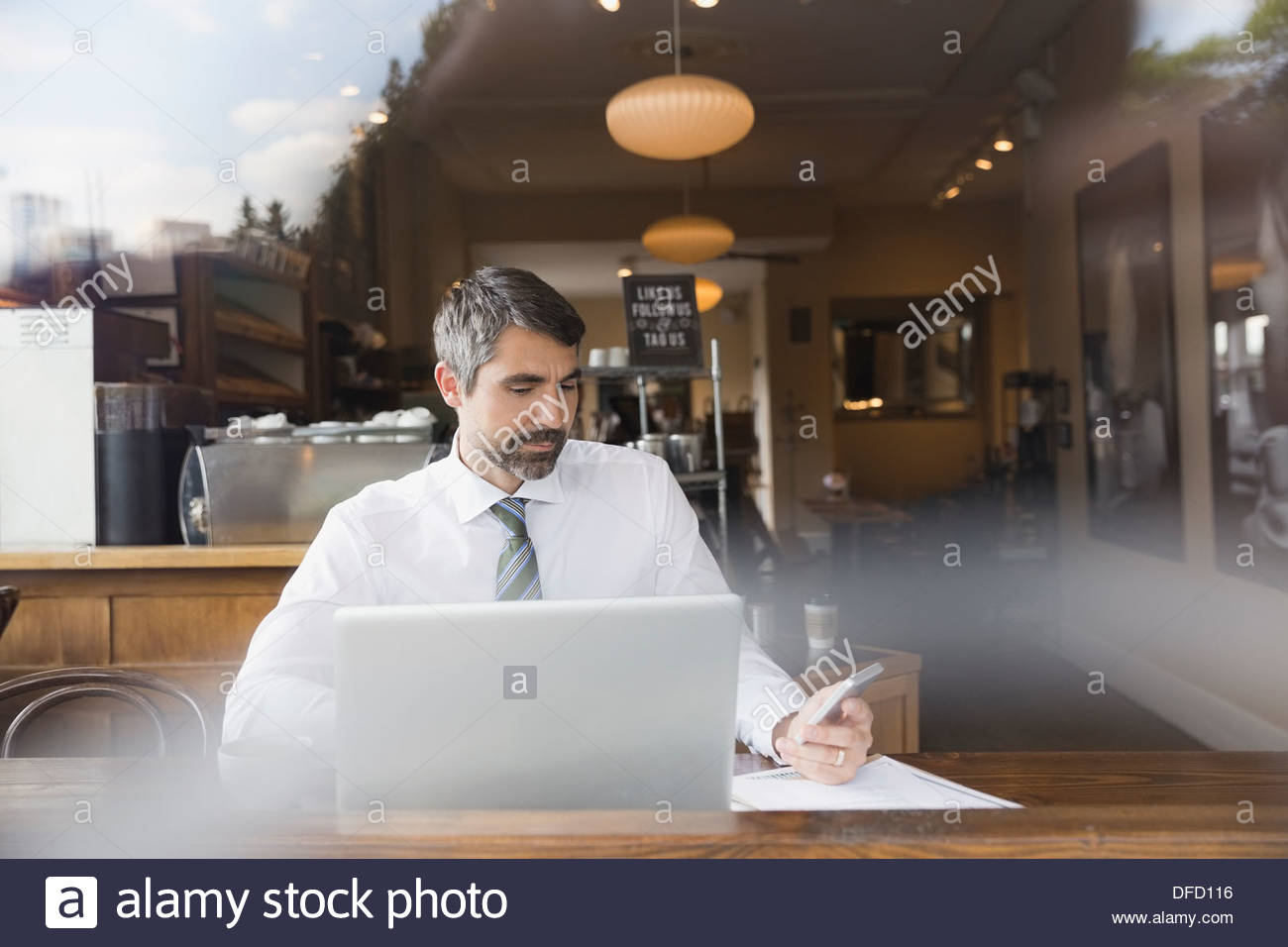 Businessman working on wireless devices in a cafe - Stock Image