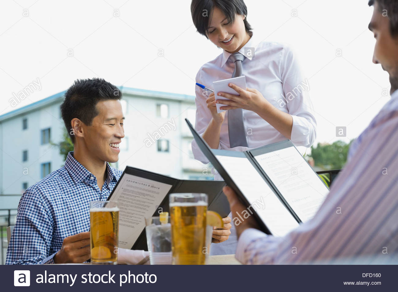 Waitress taking order from businessmen at outdoor cafe - Stock Image