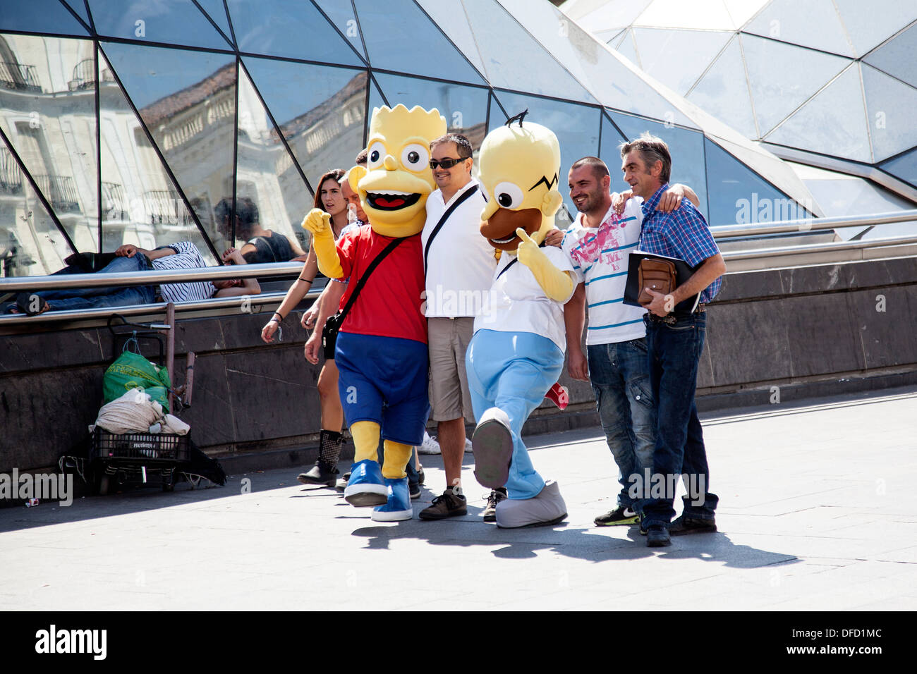 Tourist pose with street artist as the Simpsons in the Puerta del Sol, Madrid, Spain - Stock Image