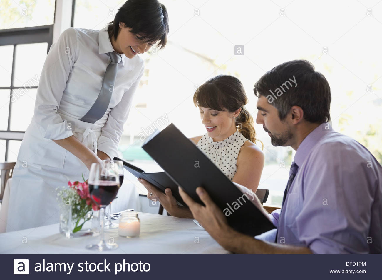 Waitress taking order from professional couple in restaurant - Stock Image