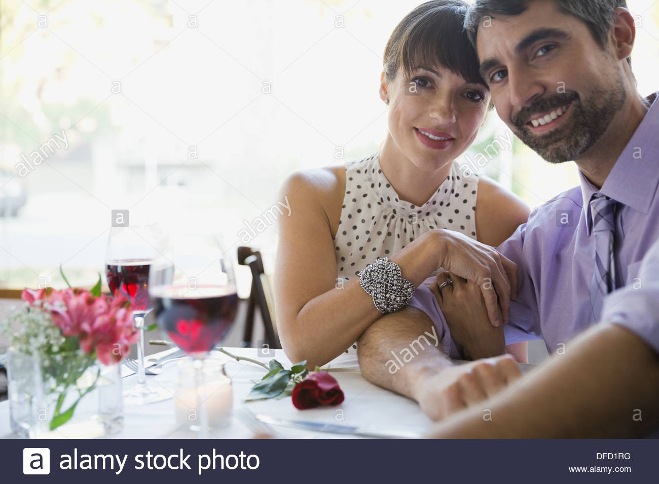 Portrait of smiling professional couple sitting in restaurant - Stock Image