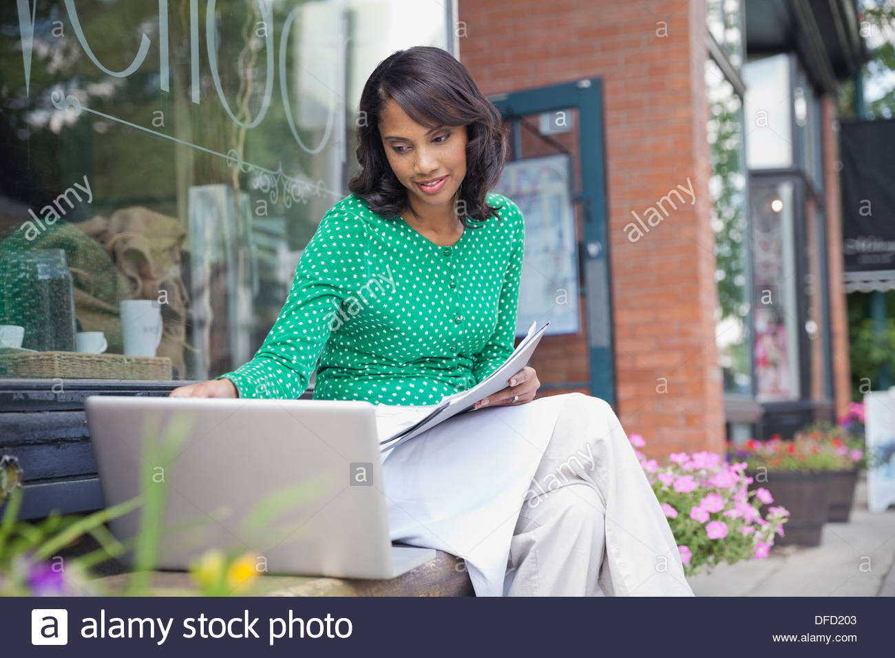 Small business owner working on laptop outside of cafe - Stock Image