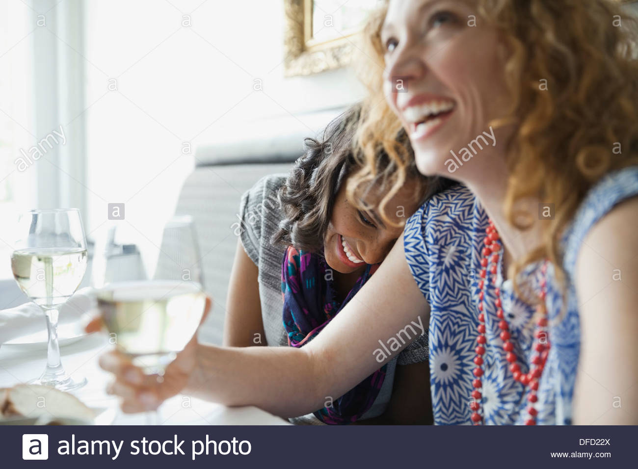 Female friends laughing while dining out - Stock Image