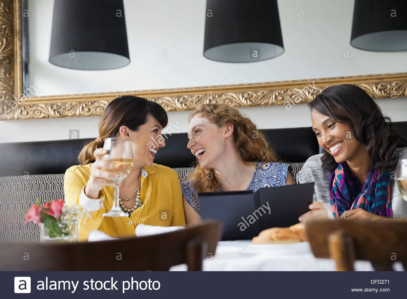 Cheerful female friends dining out - Stock Image