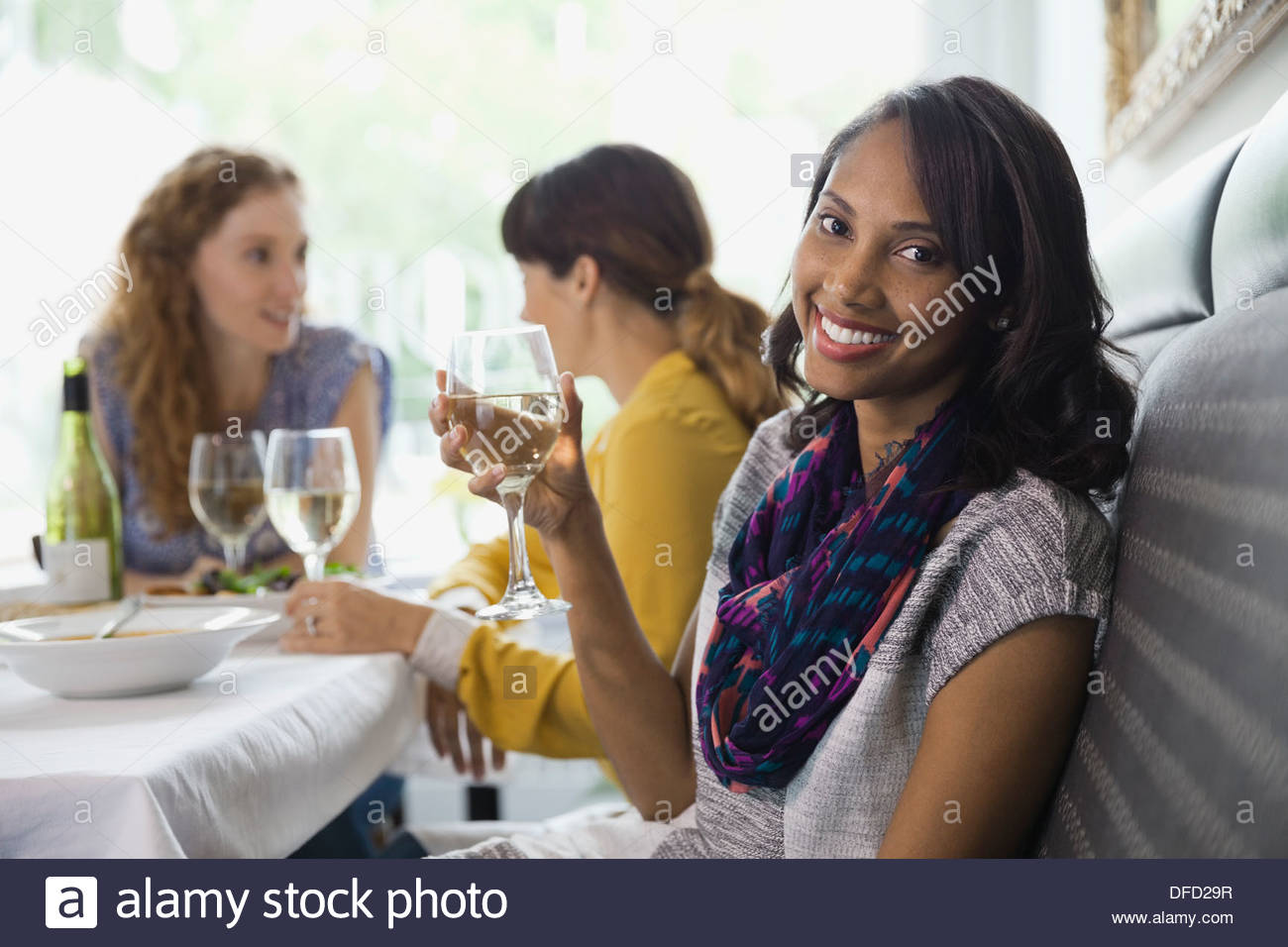 Portrait of smiling woman holding wineglass in restaurant - Stock Image