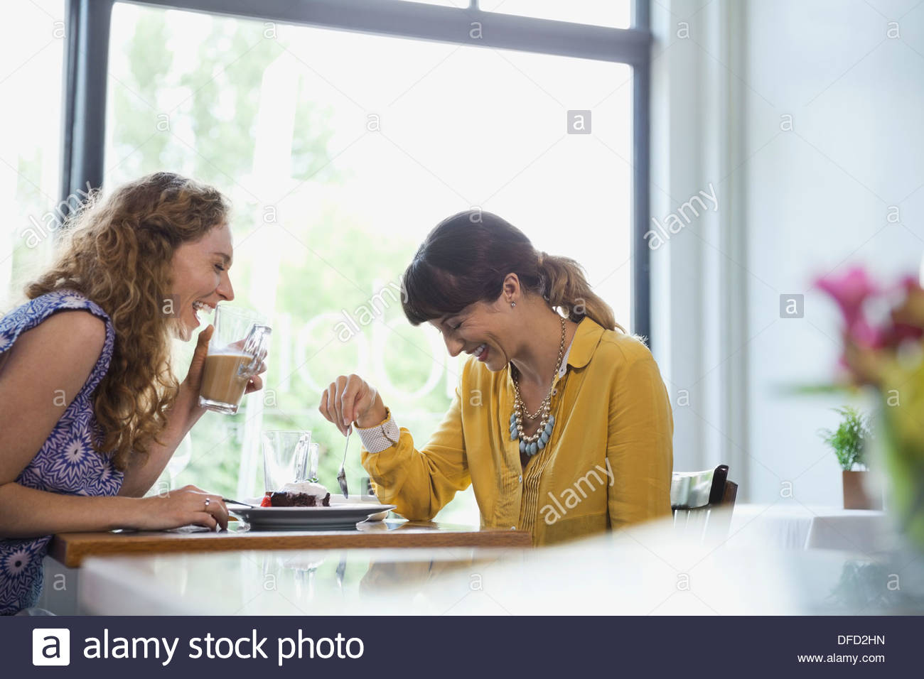Cheerful female friends laughing in restaurant - Stock Image