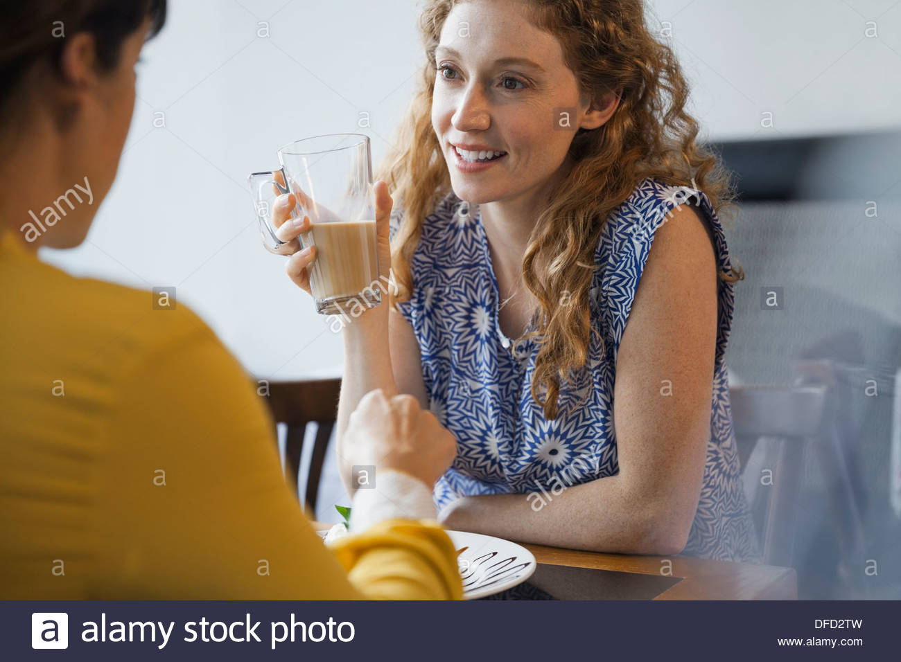 Female friends having a conversation while dining out - Stock Image