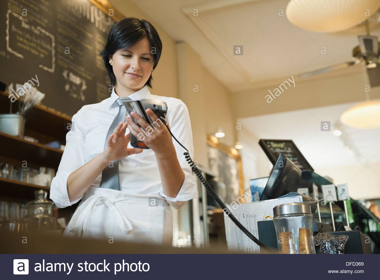 Waitress using credit card terminal in cafe - Stock Image