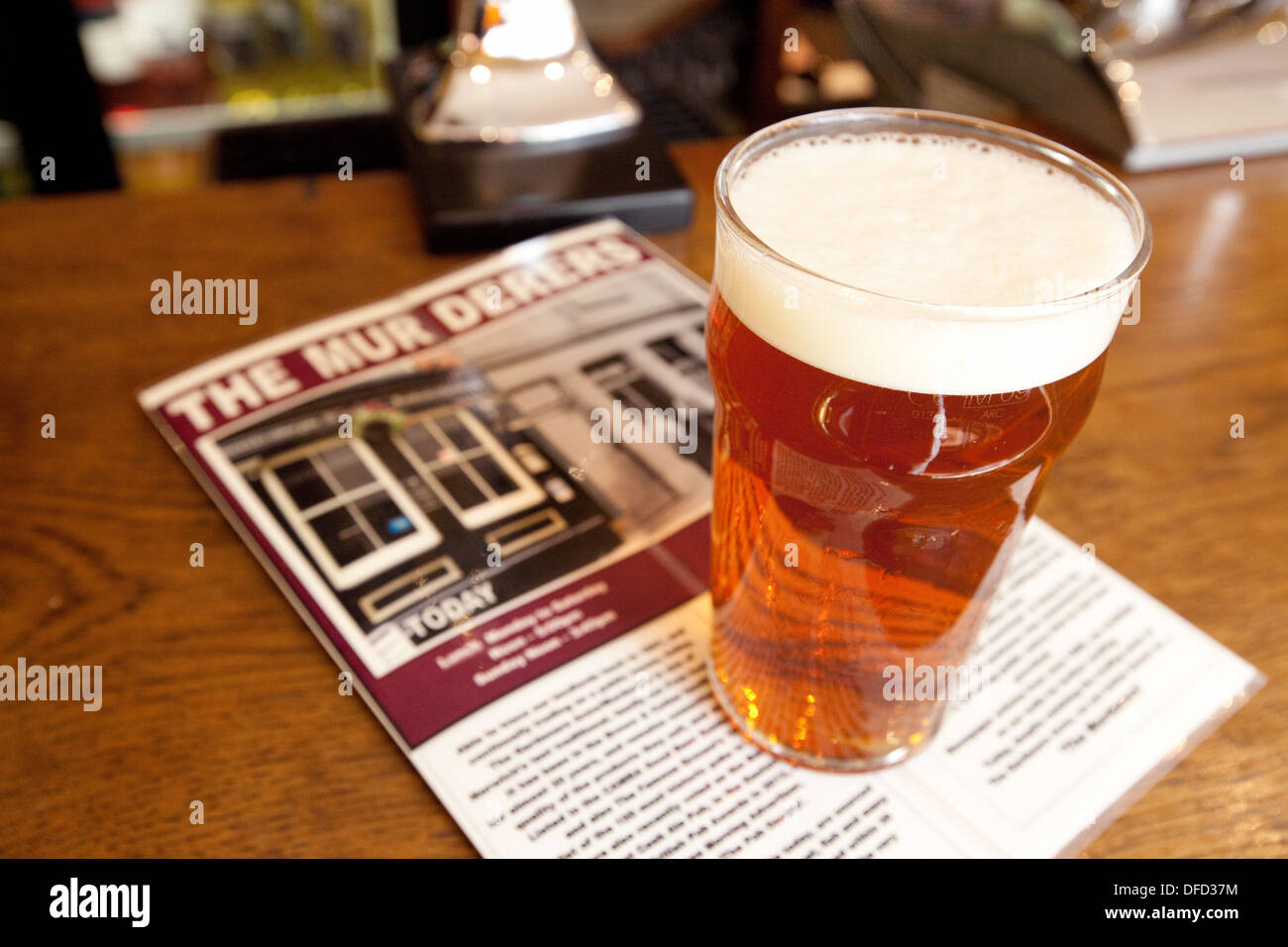 A pint of beer and the menu on the bar, The Murderers Pub restaurant, Norwich, Norfolk UK - Stock Image