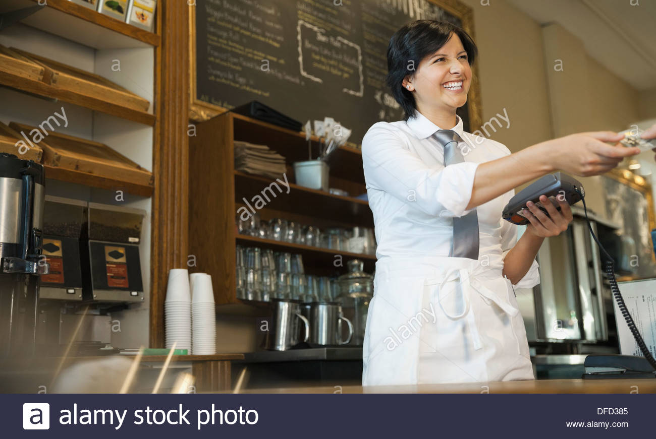 Waitress processing payment for restaurant bill - Stock Image