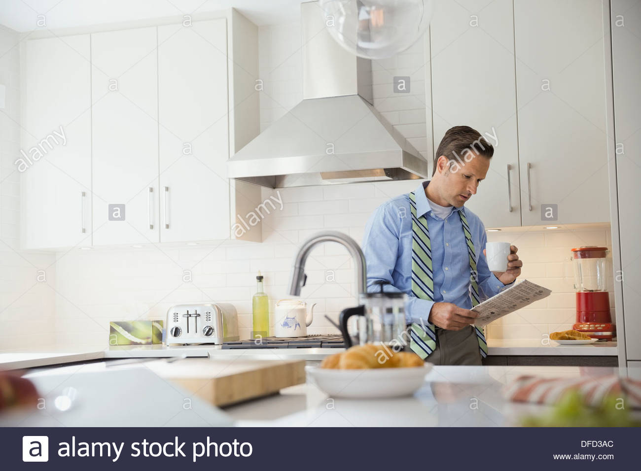 Businessman reading newspaper in domestic kitchen - Stock Image