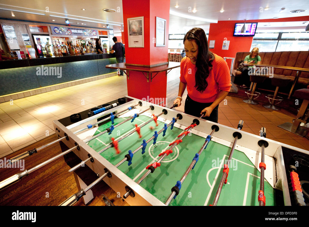 A young woman playing table football, the student union bar, UEA, University of East Anglia, Norwich, Norfolk UK - Stock Image