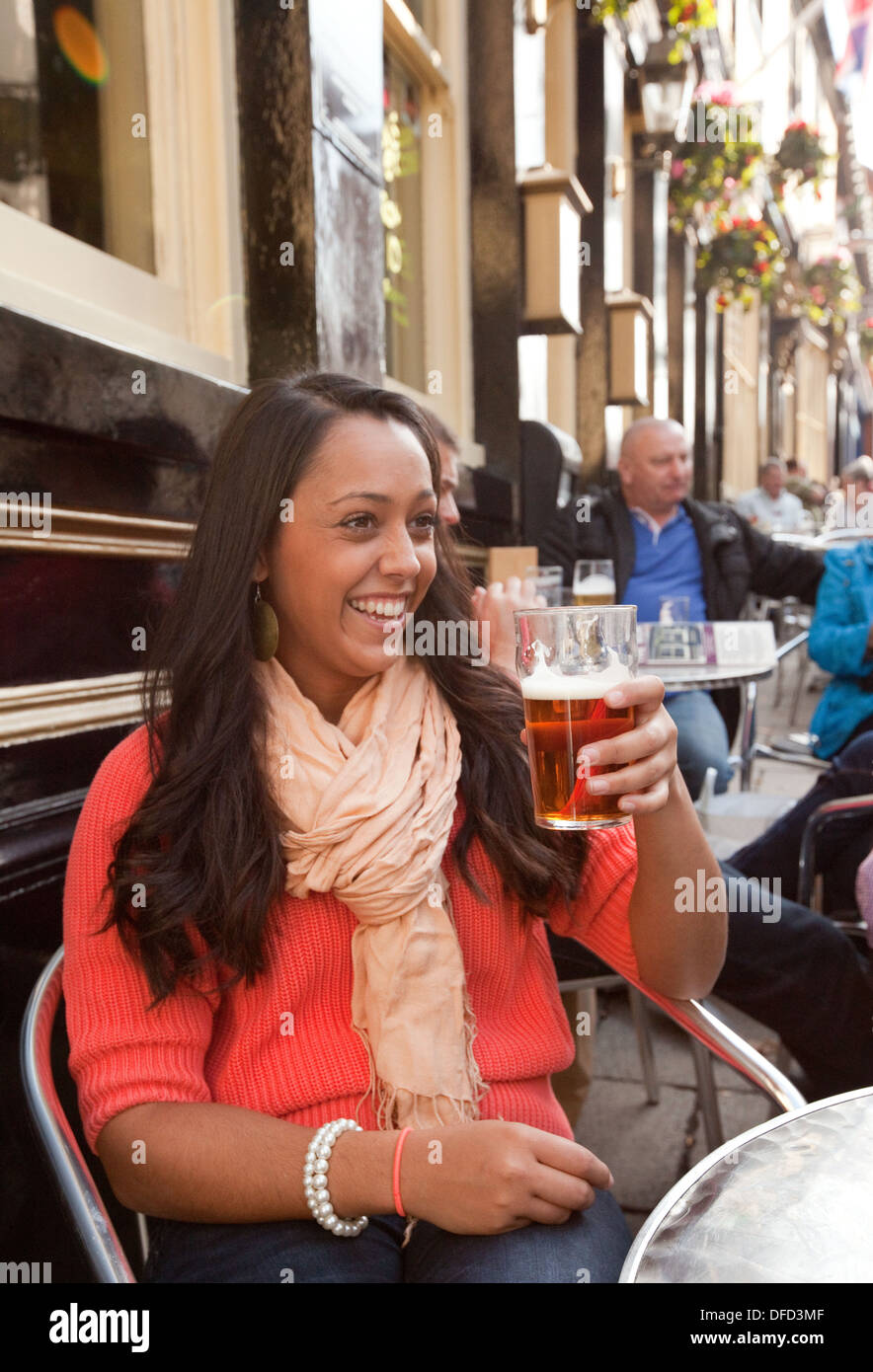 Young woman enjoying drinking a pint of beer in a pub, The Gardeners Arms, Norwich, Norfolk, England UK - Stock Image