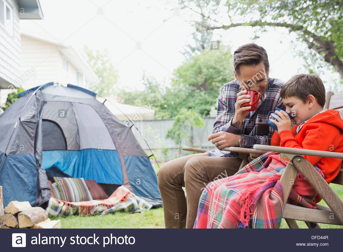 Father and son drinking hot chocolate while camping in backyard - Stock Image
