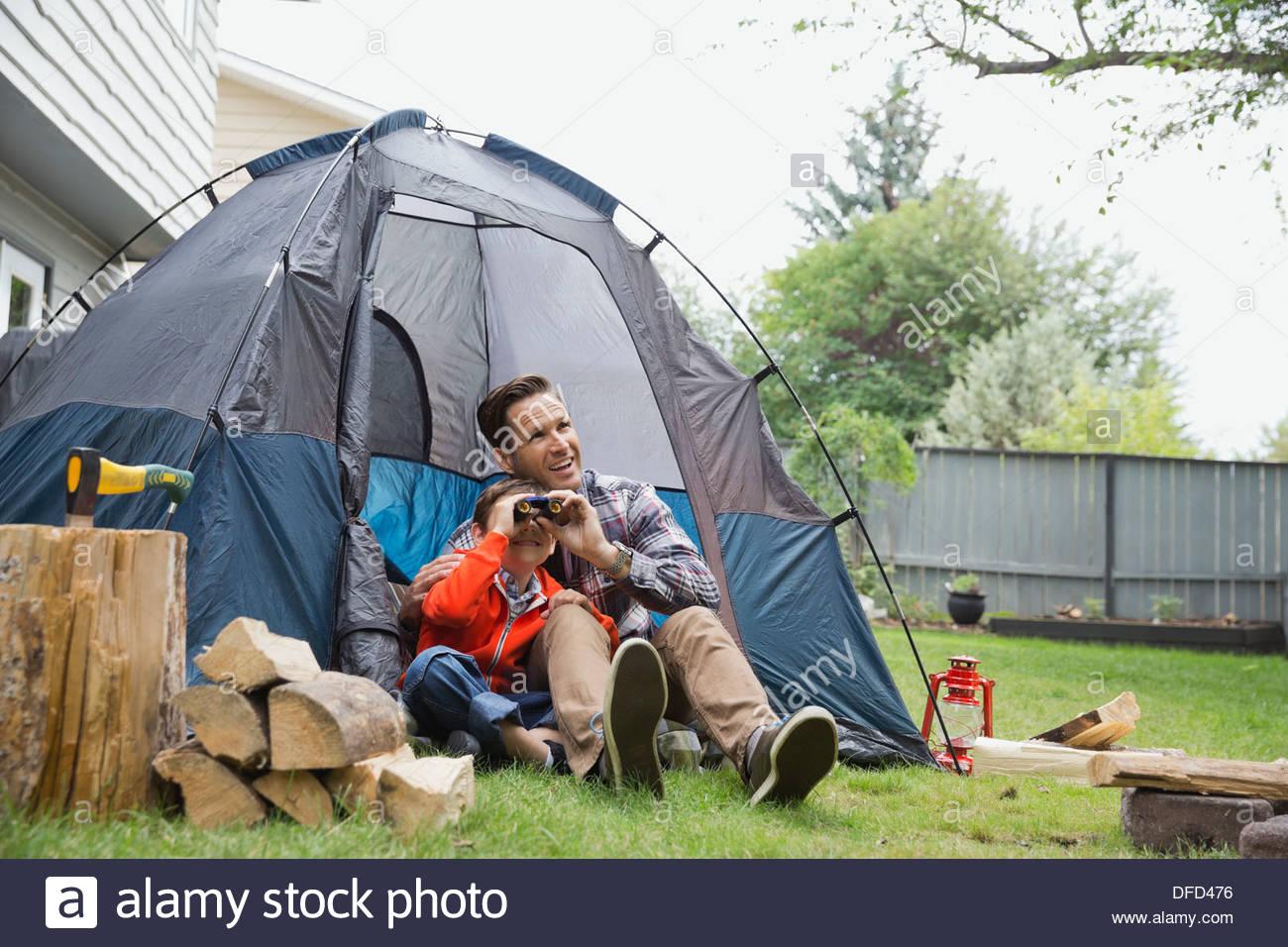 Boy looking through binoculars with father in backyard - Stock Image