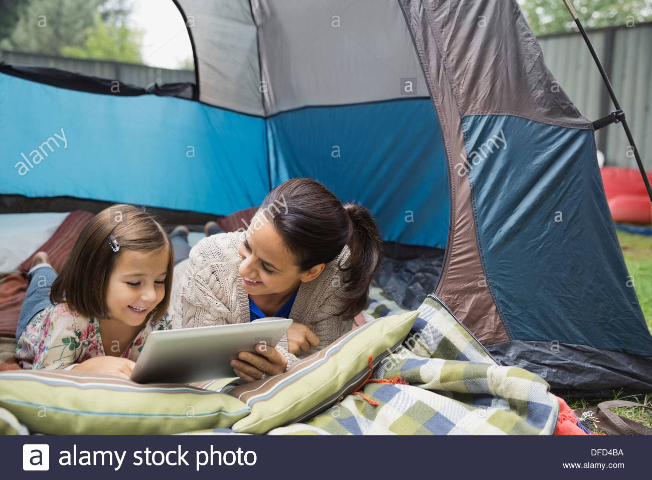 Mother and daughter using digital tablet in tent - Stock Image