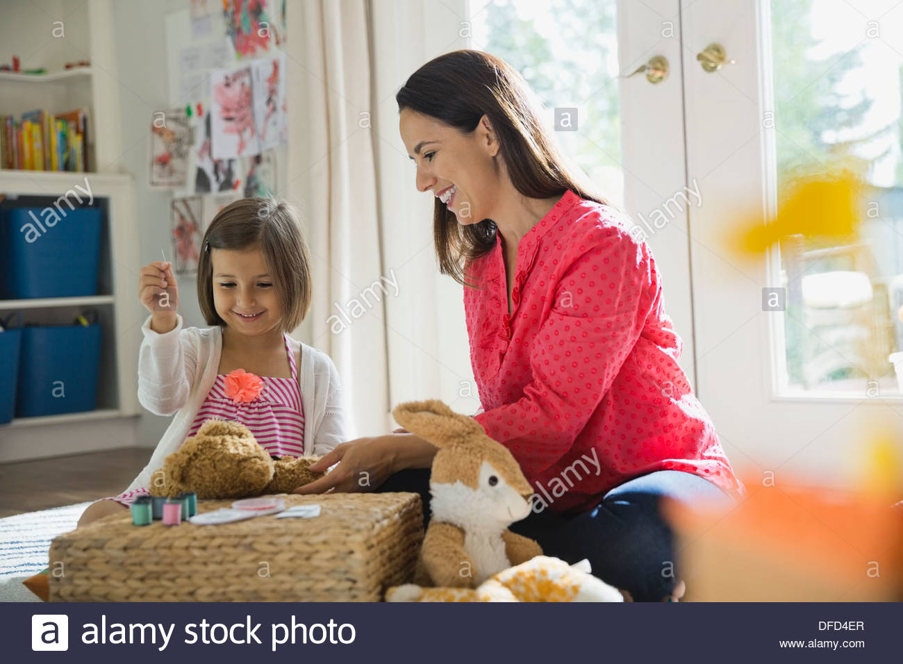 Mother supervising daughter sewing teddy bear at home - Stock Image