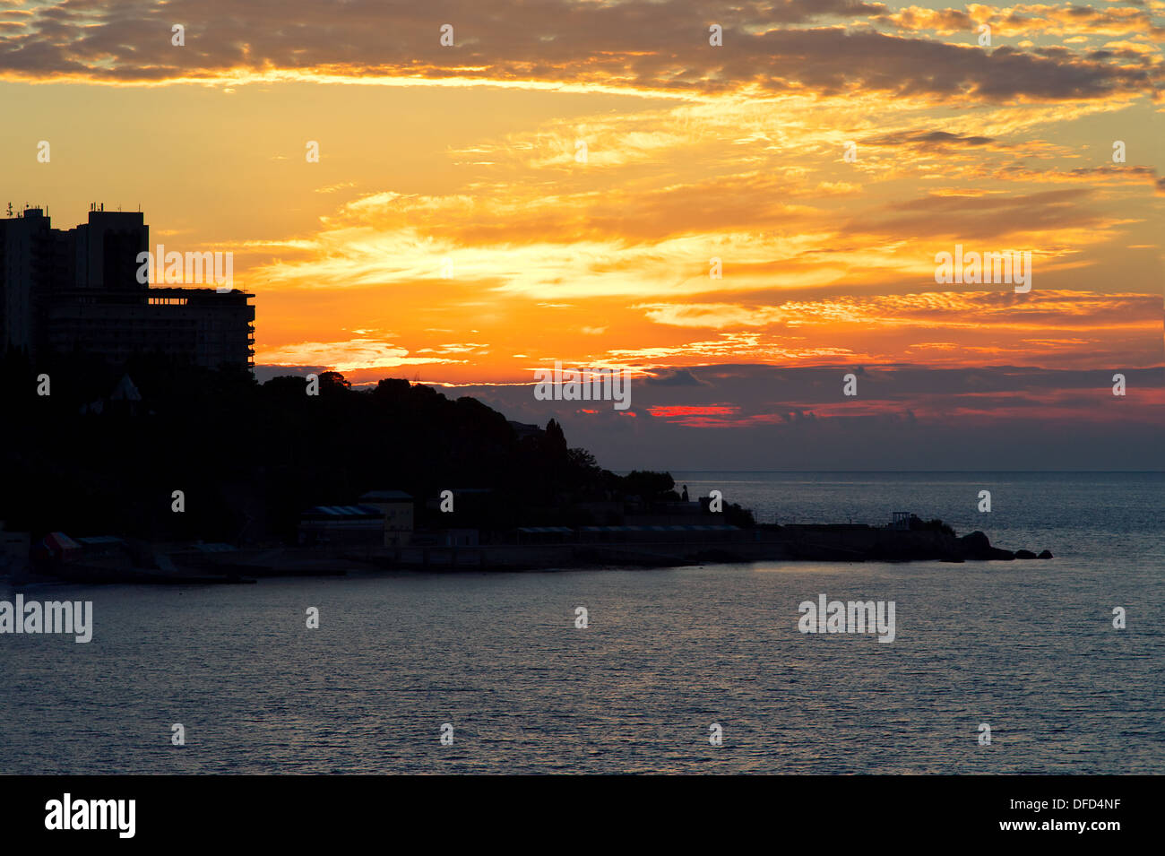 Background of dawning Sky and Sea on Sunrise with town silhouette beautiful scenery with natural orange colors - Stock Image