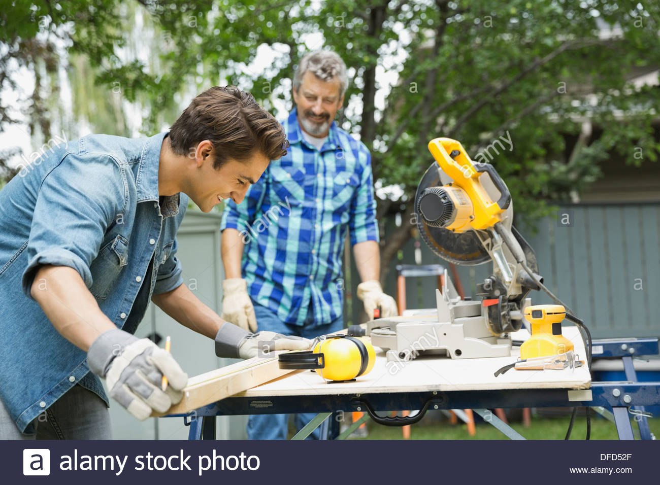 Side view of man measuring wooden plank with father in yard - Stock Image