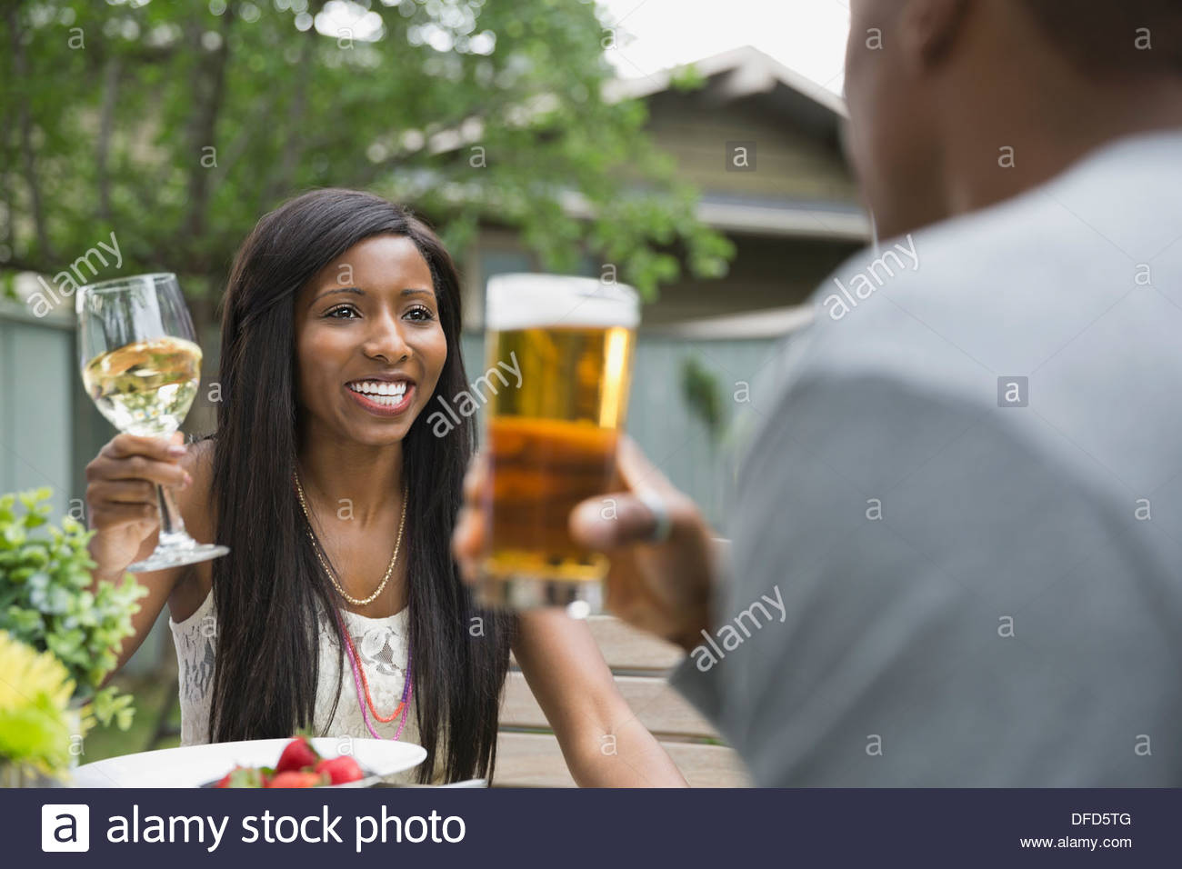 Cheerful couple enjoying a drink in backyard - Stock Image