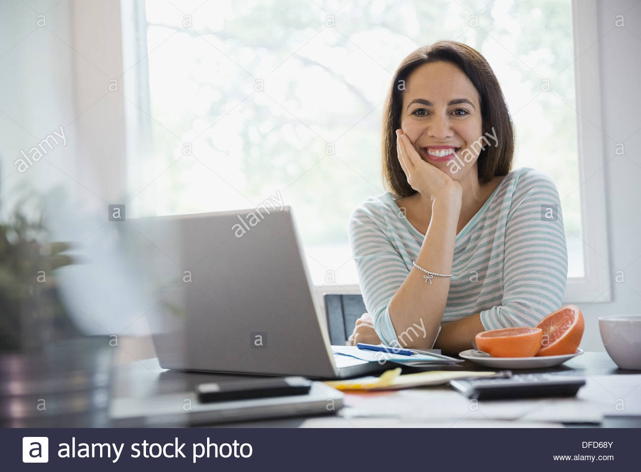 Portrait of happy woman sitting with laptop at desk in home office - Stock Image